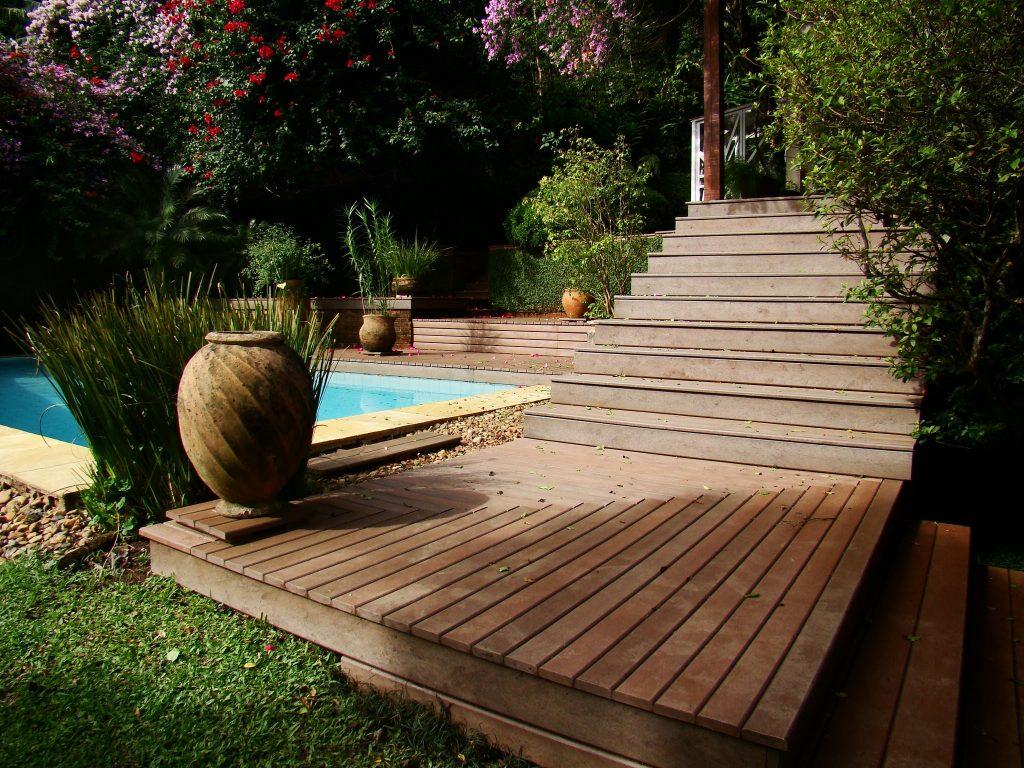 Área externa com piscina, deck de madeira plástica rewood e bastante arborizado. Há escadas também em madeira plástica que dão acesso a um pergolado sombreado.